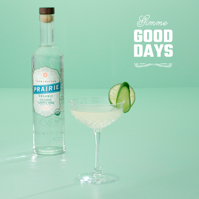 A martini glass with a lime slice on a green background
