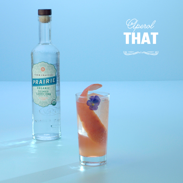 A glass with a grapefruit peel and bottle on a blue background