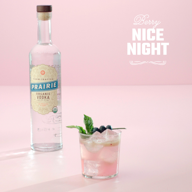 A lowball glass with a sprig on a pink background